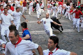 """A fighting bull runs behind participants during the Running of the Bulls in Pamplona, Spain. For eight days, bulls run through the historic heart of Pamplona in this fiesta made famous by the 1926 novel """"The Sun Also Rises"""" by Ernest Hemingway."""