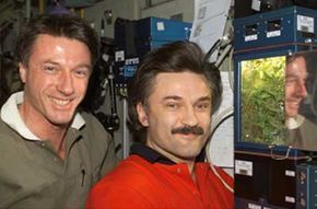 Astronauts C. Michael Foale (left) and Alexander Kaleri, part of the Expedition 8 crew aboard the ISS, pose next to the Lada greenhouse.