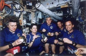 NASA's STS-74 Atlantis Space Shuttle crew enjoys a meal aboard Russia's MIR Space Station in 1996. See more astronaut pictures.