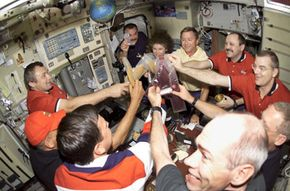 The astronauts and cosmonauts of the STS-105 toast with their space beverages.