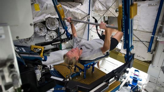 Why do astronauts have to work out on the International Space Station?