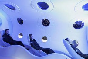 Virgin Galactic employees sit in the cabin of a prototype Virgin Galactic SpaceShipTwo spacecraft, destined to be the first-ever vehicle for space tourism.