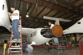 Workers prepare the spaceship for its historic flight. The large rocket motor will produce 17,000 lb of thrust.