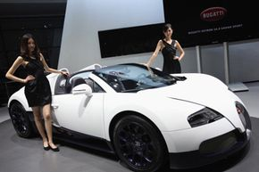 Two models pose beside the Bugatti 16.4 Super Sport during the Shanghai International Automobile Industry Exhibition in Shanghai, China.