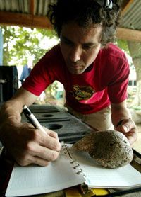 Working in Honduras, American speleologist Matthew Kalch copies down markings found on a seashell discovered in the Hato Viejo cave in 2006.