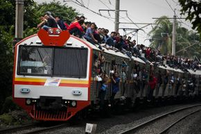 An extreme version of train surfing in Jakarta, Indonesia as hundreds ride the roof due to overcrowded trains and lack of funds to buy tickets.