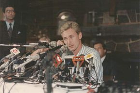A visibly distraught Wayne Gretzky sits at the press conference where his trade from the Edmonton Oilers to the Los Angeles Kings is announced in 1988.