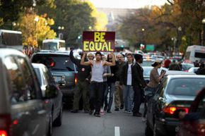 Demonstrators from the Occupy DC movement shut down rush hour traffic as they march through downtown Washington.