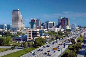 "The Orlando skyline rises above the traffic on Interstate 4, a highway that runs east to west through central Florida. The area surrounding the highway is often referred to as the ""I-4 Corridor."""