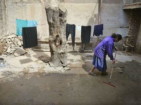 A Jewish woman in Baghdad, Iraq, washes the floors in her home in preparation for Passover.