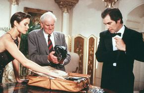 """Bond (Timothy Dalton) meets with Q (Desmond Llewelyn) to receive his case full of gadgets in """"License to Kill."""" The gadgets in this film include a camera that fires a deadly laser out of its flash component and a """"signature gun"""" that Q has programmed for Bond's use alone."""