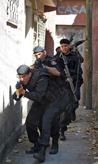 """Members of Brazil's Militarized Police patrol an alley in the squatter village of Cidade Alta (known as the """"City of God"""") in Rio de Janeiro in 2007."""