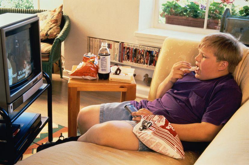 fat boy eating junk food watching tv