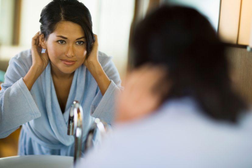 asian woman looking in mirror