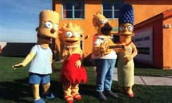 """Bart, Lisa, Homer and Marge show off a full-size replica of """"The Simpsons"""" house."""