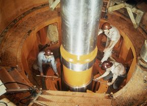 Workers check the alignment of a turbine shaft at the top of the guide bearing at the Watts Bar hydroelectric dam, 1942.
