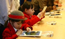 Kids play with tablets at an Apple Store in London.