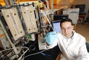 Georgia Tech graduate student Jeffrey Drese displays a tubular reactor filled with the HAS adsorbent dispersed in sand.