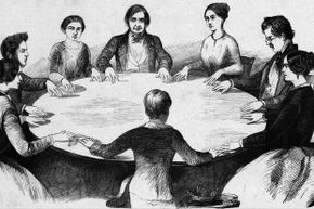 A woodcut of table rapping as practiced in the first half of the 19th century under the influence of the Fox sisters.