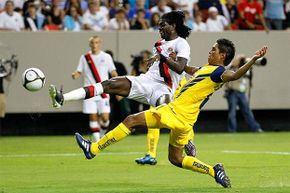 Emmanuel Adebayor (white shirt) of Manchester City takes a shot on goal against Pablo Zabaleta of Club America (Mexico) at a soccer match in Atlanta. Neither player would be subject to U.S. tax for any money earned during their tour of the country.