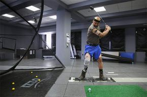 U.S. military veteran and amputee Lloyd Epps swings a driver while at the gait and motion analysis lab at the VA hospital in New York City. Epps lost his leg to an infection and wears a high-tech custom prosthetic.