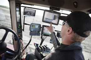 This farmer monitors several things via GPS and other high-tech tools in his tractor.