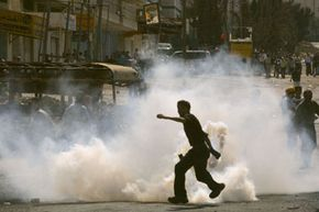 A Palestinian throws a tear gas grenade back at Israeli soldiers during a 2001 clash on the outskirts of the West Bank town of Ramallah.