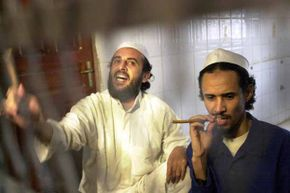 Jamal Mohammed al-Bedawi (L) shouts from behind bars and Fahd al-Quso (R) looks on as they hear the verdict in Yemen at the end of the trial of six militants charged with the October 2000 bombing of the Navy destroyer USS Cole.