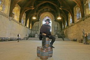 An actor dressed as Guy Fawkes sits atop fake barrels of gunpowder in Westminster Hall in the Houses of Parliament in London, as the British Parliament marked the 400th anniversary of the discovery of the Gunpowder Plot in 2005.