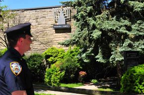 A police officer stands guard outside Riverdale Temple after FBI and New York City law enforcement agencies stopped an attack on two temples in the Bronx on May 20, 2009.