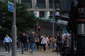 Extras run across the street during the filming of a scene for 'Transformers: Age of Extinction' in Hong Kong's financial Central district in 2013.