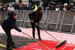 Two production assistants clear snow from the red carpet during arrivals of the London judges for 'Britain's Got Talent' in 2013.