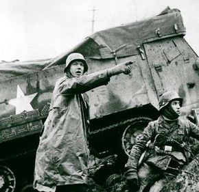 German soldiers advance past a knocked-out U.S. halftrack during the Battle of the Bulge in December 1944.