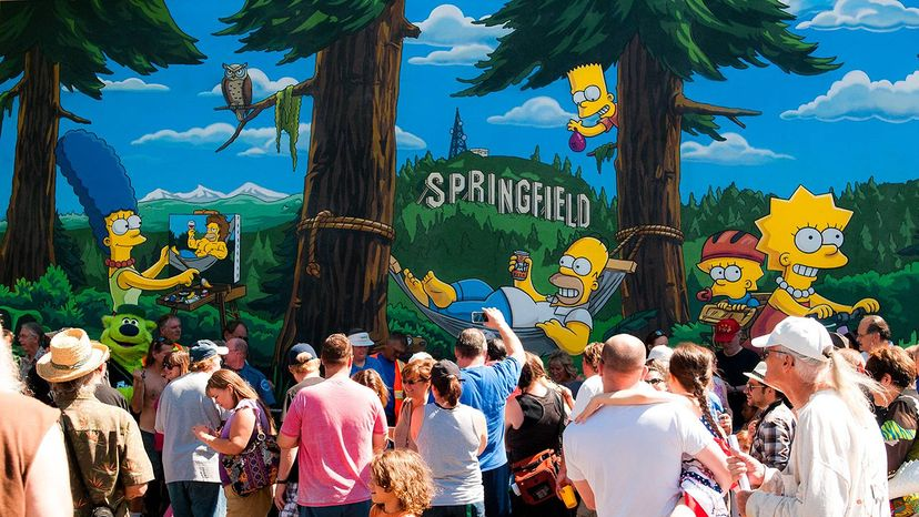 People gather in front of a Simpsons mural in Springfield, Oregon, the city many people once believed was the namesake of the animated Springfield. FOX via Getty Images