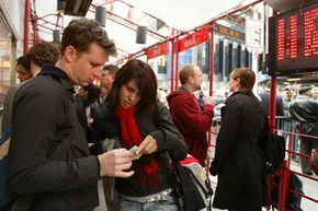 """Mario Voegeli and Angela Harp of Zurich, Switzerland, check their tickets to """"The Glass Menagerie,"""" after purchasing them at the TKTS booth in Times Square in New York."""