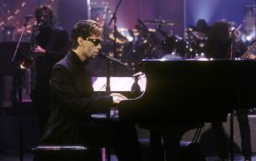 Prince (then known by an unpronounceable symbol) performs on the David Letterman Show in 1996, with the word 'slave' written on his cheek.