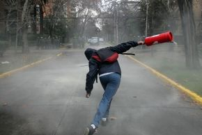 That student protester is actually throwing a regular fire extinguisher. That's not quite the same thing as one that's designed to be lobbed at a fire.