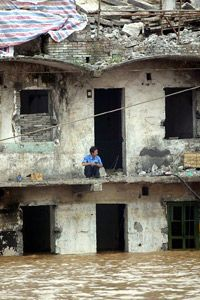 This man still lives in a half-demolished building nearly submerged by the Yangtze's rising waters.