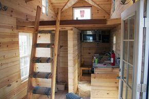 This tiny house interior shows a ladder without rails going up to the sleeping loft. Some say this is hazardous.
