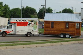 A U-Haul van tows a tiny house to its next destination. Tiny houses don't tow as easily as RVs.