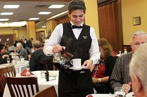 Whittier Vocational Technical High School student waitress Younique Martin pours coffee during lunch at Poet's Inn Restaurant at the high school in Haverhill, Massachusetts. Tip income must be reported to the IRS.