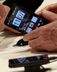 A visitor examines an HTC smartphone at the Vodafone stand at the CeBIT Technology Fair on March 3, 2010 in Hannover, Germany.