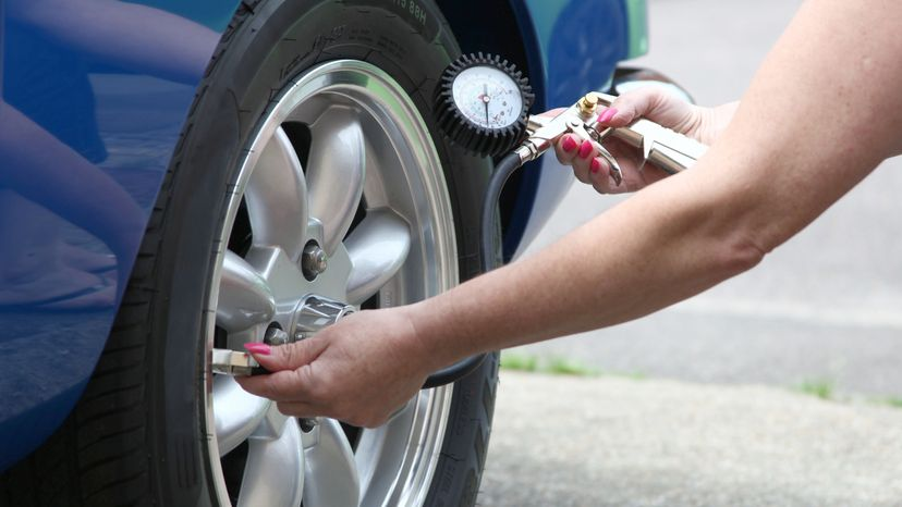 Woman Checking Tire Pressure with Gauge