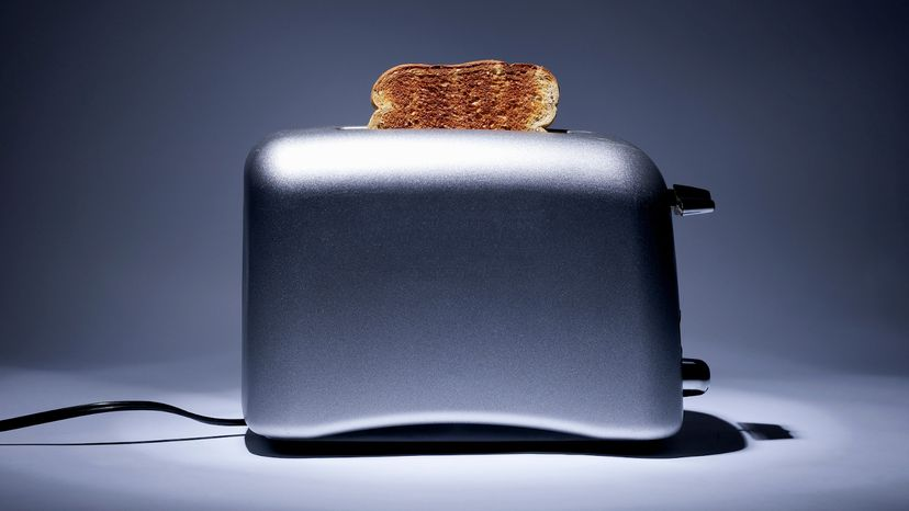 Silver colored toaster with single slice of toast
