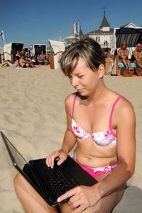 Swiss tourist Katja Krueger is seen with a laptop at the Baltic Sea beach of Ahlbeck, island of Usedom, northern Germany.