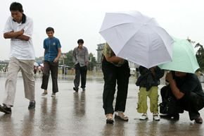 A family seeking shelter under umbrellas from the driving rain on Tiananmen Square in Beijing, China.