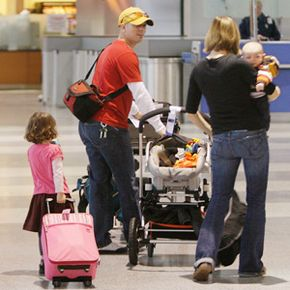 Pushing a luggage cart and pulling a baby stroller, Justin Sirotin looks back at his wife Alicia Bell, carrying their son Logan, 3 months, and followed by their daughter Jordan, 3, as they walk through Logan International Airport in Boston.