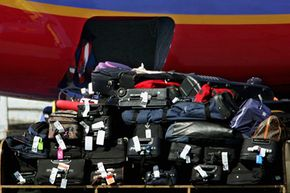 Baggage handlers load checked luggage aboard a Southwest Airlines jet as a tram carrying more bags passes in the foreground at Los Angeles International Airport.