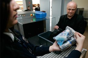 An airport security officer shows a transparent re-sealable freezer-type plastic bag containing a passenger's carry-on liquids, pastes, gels, creams and aerosols.