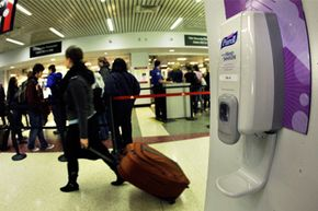 A traveler wheels luggage past one of many hand sanitizer dispensers hung on walls at Logan International Airport in Boston.